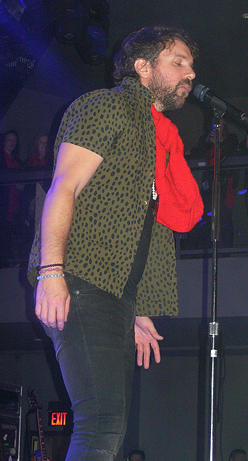 Colin onstage in London, with a red scarf.